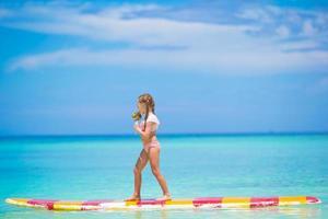 niña con piruleta en una tabla de surf en el mar
