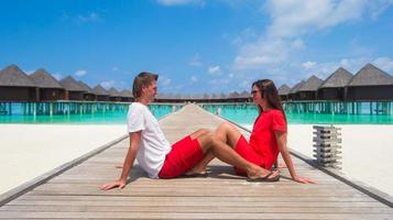 Maldives, South Asia, 2020 - Couple sitting on a beach jetty