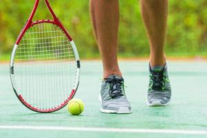 Close-up of sneakers and a tennis racquet and ball