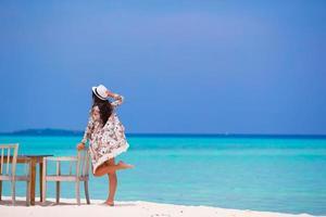 mujer posando con una silla en la playa