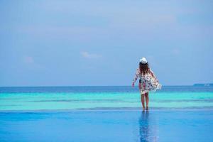 mujer estar de pie, en, borde, de, piscina infinita