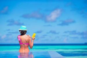 mujer aplicar protector solar en una piscina foto