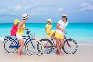 Familia divirtiéndose en bicicleta en la playa