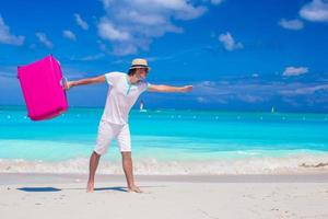 Man with pink luggage on a tropical beach