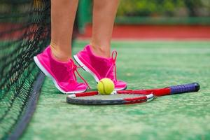 Close-up de zapatillas cerca de la raqueta de tenis y pelota.