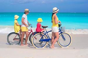 Family of four riding bicycles on a tropical beach