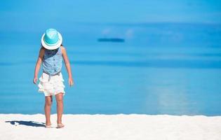 chica con sombrero en una playa de arena blanca