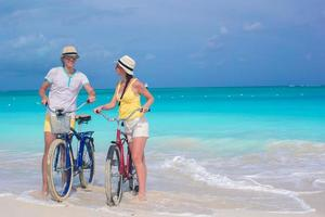 Couple riding bikes in ocean water