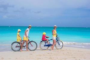 Family riding bikes on a white beach