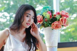 mujer asiática sentada junto a un jarrón de flores