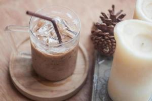 Iced coffee with a candle and pinecone
