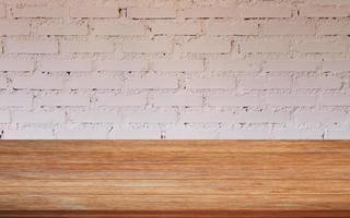 mesa de madera con una pared de ladrillo blanco