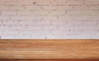mesa de madera con una pared de ladrillo blanco foto