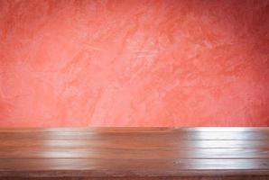 mesa de madera contra una pared roja foto
