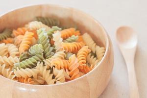 Raw fusilli pasta in a wooden bowl