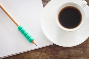 Pencil on a notebook with a coffee cup