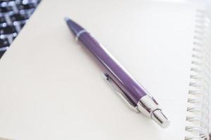 primer plano, de, un, cuaderno, con, un, lápiz púrpura foto