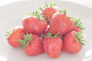 Bunch of strawberries on a white plate photo