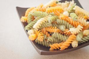 Fusilli pasta on a black plate