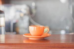Taza de café naranja en la cafetería. foto