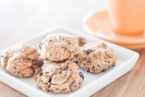 Close-up de galletas saludables en una placa blanca con una taza de café foto