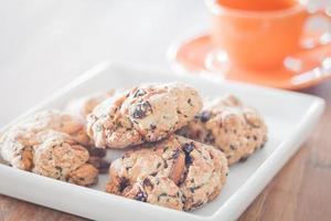 Close-up de galletas de nueces mixtas con una taza de café naranja foto