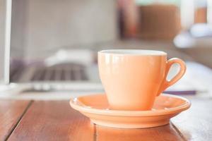taza de café naranja en una estación de trabajo