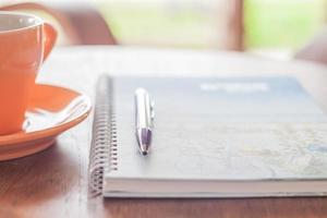 taza de café con un bolígrafo y un cuaderno de espiral foto