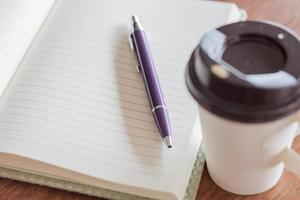 bolígrafo y cuaderno con una taza de café foto