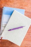 bolígrafo y dos cuadernos en una mesa de madera foto