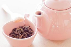 té oolong en una taza de cerámica con una jarra y una cuchara de madera foto