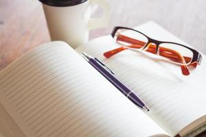 Notebook with a pair of glasses, a pen, and coffee