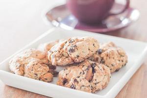 Close-up de galletas de nueces mixtas con una taza de café púrpura foto