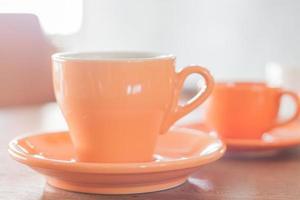 taza de café naranja y una mini taza de café naranja
