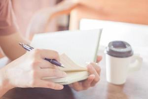 persona sosteniendo un cuaderno y un bolígrafo foto