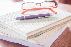 Pen and eyeglasses on notebooks