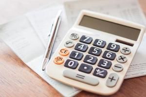 Calculator and pen with financial papers