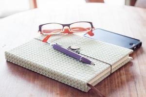 cuaderno y bolígrafo con un teléfono inteligente en una mesa de madera foto