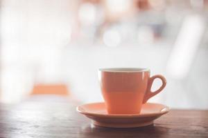 Taza de café naranja sobre una mesa de madera
