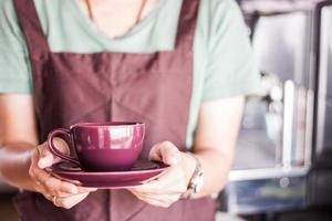 Barista holding a purple cup