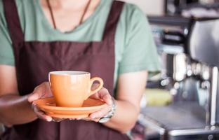 Barista presents freshly brewed coffee