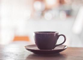 Taza de café púrpura sobre una mesa de madera