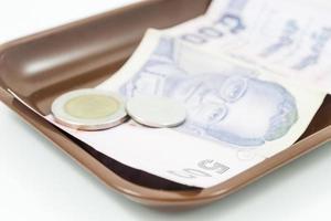 Billetes y monedas tailandesas en una bandeja