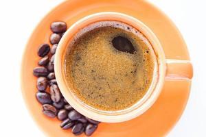 Taza de espresso y café tostado sobre un fondo blanco. foto