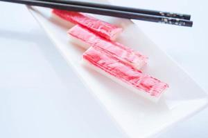 Crab sticks with chopsticks on a white plate photo