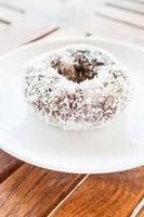 Chocolate coconut donut on a white plate