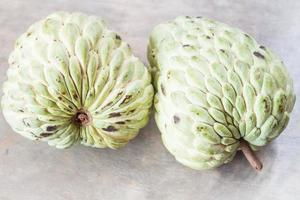 Couple of custard apples on a gray background photo