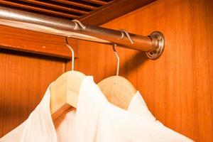 White bathrobes hanging on wooded hangers