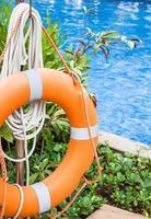 Orange lifebuoy near a swimming pool