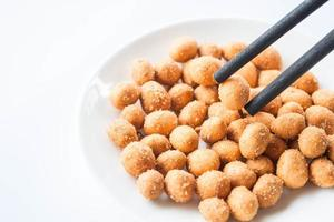Chopsticks holding spicy peanut snack
